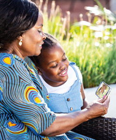A woman shows a little girl a Bible-based video