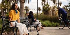 Žena sedí v parku na lavičce a přemýšlí