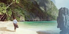 一名穿西装的男子赤脚走在沙滩上,欣赏着大海的美景