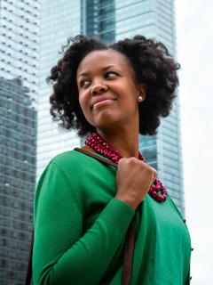 Una mujer feliz en una gran ciudad caminando con seguridad