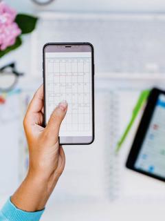 Una mujer mirando un calendario en su teléfono