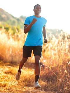 A young man smiling as he is running outdoors.