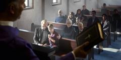 Un sacerdote sosteniendo una Biblia mientras dirige un sermón de funeral en una iglesia