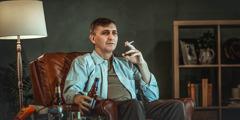 Un homme, assis dans son salon, a une cigarette dans une main et une bouteille de bière dans l'autre.