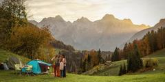 Une famille fait du camping à la montagne. Ils font un selfie, avec les montagnes en arrière-plan.