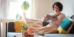Une femme, confortablement assise dans un canapé, lit la Bible.
