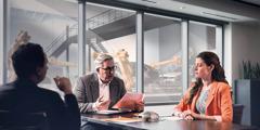 Dos hombres entrevistando a una mujer para trabajar en una fábrica de automóviles. Ella está tensa.