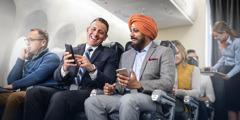 Un hombre blanco y un hombre de la religión sijista sentados juntos en un avión conversando alegremente.