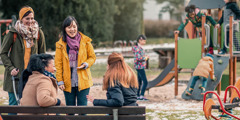 Four women of different racial backgrounds talking and laughing as their children play together at a playground.