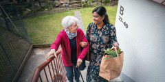 An Indian woman helping an older Caucasian woman up the stairs with her groceries.