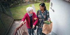 Une Indienne aide une dame âgée blanche à monter un escalier tout en lui portant ses courses.