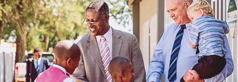Johny y Gideon saludando a los niños frente al Salón del Reino.