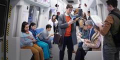 คนในรถไฟใต้ดินกำลังดูอุปกรณ์อิเล็กทรอนิกส์ในมือพวกเขา