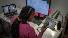 Nastolatka robi wiele rzeczy naraz. Pisze wiadomość na smartfonie, prowadzi wideorozmowę z przyjaciółką i uczy się, korzystając z komputera i książki.