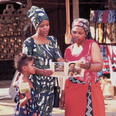 One of Jehovah's Witnesses and her little girl preach to a woman at a shop