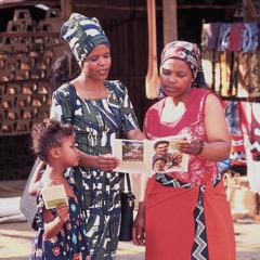 Salah seorang Saksi-Saksi Yehuwa dan putrinya mengabar kepada seorang wanita di toko