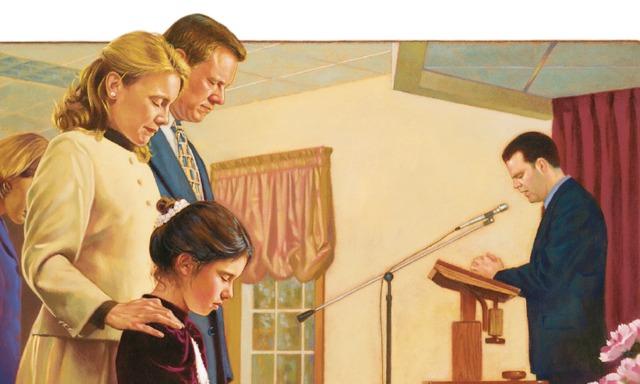 Una familia escucha una oración en la reunión