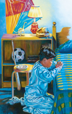 A boy kneels beside his bed and prays