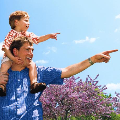 一個仁愛的父親把兒子馱在肩膀上,父子倆一起看上帝創造的東西