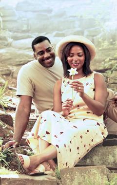 Marido e esposa sentados num jardim, olhando para uma flor