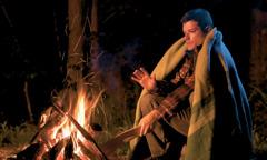 Egy férfi atűznél melegszik, és fát tesz atűzre