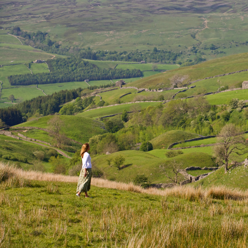 Una mujer caminando sobre un tranquilo campo verde