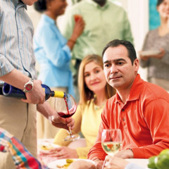 A man deciding whether or not he will drink a glass of wine at a gathering