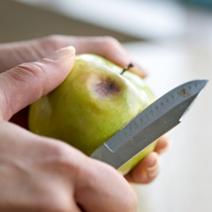 Cutting a rotten spot out of a piece of fruit