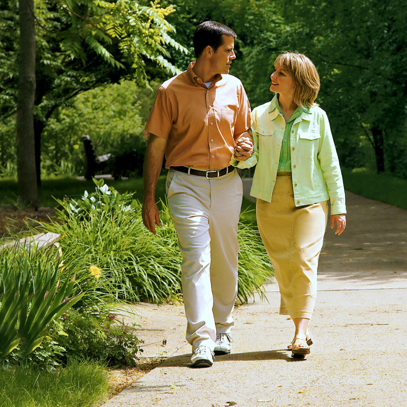 Un matrimonio caminando alegres en un parque brazo con brazo