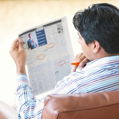 A man looking in a newspaper for potential work