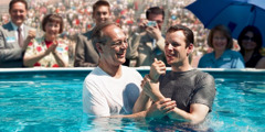 A man being baptized in water at a large Christian convention