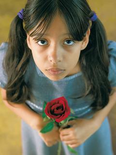 Ein kleines Mädchen hält eine Rose in den Händen