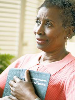 Eine Frau drückt ihre Bibel an ihr Herz und lächelt