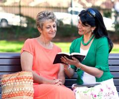 Eine Zeugin Jehovas liest einer Frau einen Text aus der Bibel vor