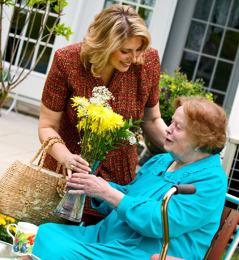 Mladší sestra dává starší sestře kytici