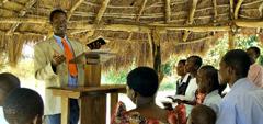 En kretstilsynsmann taler til en menighet i Uganda