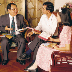 One of Jehovah's Witnesses studies the Bible with a couple