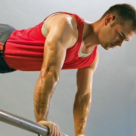 Mężczyzna ćwiczy, żeby wzmocnić swoje mięśnie