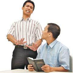 Seorang pria membaca Alkitab dan pria yang lain menunjukkan bahwa dia tidak suka