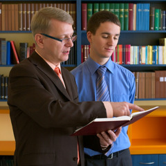 Et af Jehovas Vidner der hjælper en ung mand med at foretage research