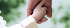En far holder hånden til den lille gutten sin