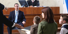 A man on trial in a courtroom with his family looking on