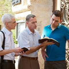 Two of Jehovah's Witnesses in the house-to-house ministry share a scripture with a man