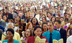 A large, diverse crowd of Jehovah's Witnesses singing