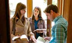 Two young Christian sisters sharing the Bible's message with a young man