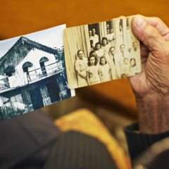 Antônio Simões holds two photos of the first congregation in Manaquiri, Amazonas State, Brazil