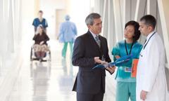 عضو في لجنة الاتصال بالمستشفيات يتحدث الى طبيبين في مستشفى