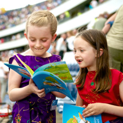 Two young girls looking through the brochure My Bible Lessons at a convention