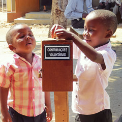 Two young boys putting money into a contribution box