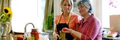 Une belle-mère regarde d'un air désapprobateur la façon de cuisiner de sa belle-fille